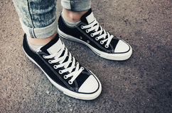 Black and white new sneakers, teenager feet Stock Image
