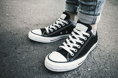 Black and white new sneakers, teenager feet Royalty Free Stock Photos