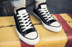 Black and white new sneakers, teenager feet Stock Photos