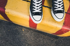 Black and white new sneakers, teenager feet Royalty Free Stock Image