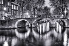 Black and White Night View of Amterdam Cityscape with One of Its Canals. With Illuminated Bridge and Traditional Dutch Houses Royalty Free Stock Images
