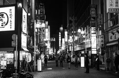 Black and white of nightlife on a busy street in Tokyo full of illuminated advertisements Stock Photos