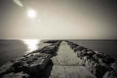 Black and white nostalgic tranquil seascape panorama with stony pier. Stock Photos