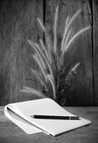 Black and white  notebooks with flower foxtail weed  on wooden b Royalty Free Stock Images