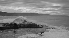 Black & white ocean and waves crashing on a cloudy day stock photo