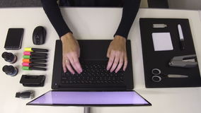 Black and white office supplies. Woman typing on laptop stock video