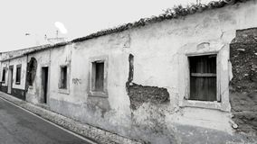 Monochrome abandoned old houses in Portugal. Long deserted and boarded up houses in Loule in Portugal, with decayed walls and a general sense of dilapidation stock photo