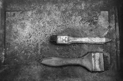 Black and white of old used paint brush on metal plate Royalty Free Stock Photos
