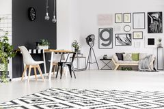 Black and white open space. Black and white chair at dining table in open space interior with posters above settee Royalty Free Stock Photos