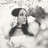 Beautiful young woman surrounded by flowers of apple-tree. Black and white outdoor fashion photo of beautiful young woman surrounded by flowers of apple-tree Royalty Free Stock Photo