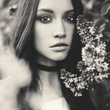 Beautiful young woman surrounded by flowers of lilac. Black and white outdoor fashion photo of beautiful young woman surrounded by flowers of lilac. Spring Stock Photos