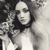 Beautiful young woman surrounded by flowers of lilac. Black and white outdoor fashion photo of beautiful young woman surrounded by flowers of lilac. Spring Royalty Free Stock Photos