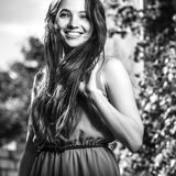 Black-white outdoor portrait of beautiful emotional young brunette woman in stylish dress Stock Photo