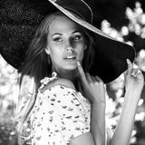 Black-white outdoor portrait of beautiful young blonde sexy woman in black classic hat Royalty Free Stock Image