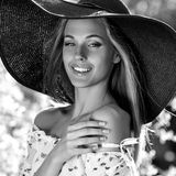 Black-white outdoor portrait of beautiful young blonde sexy woman in black classic hat Stock Images
