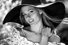 Black-white outdoor portrait of beautiful young blonde sexy woman in black classic hat Royalty Free Stock Images