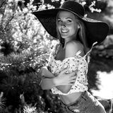 Black-white outdoor portrait of beautiful young blonde sexy woman in black classic hat Stock Photo