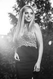 Black-white outdoor portrait of beautiful young smiling blond woman in stylish dress Royalty Free Stock Photography