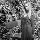 Black-white outdoor portrait of beautiful young smiling blond woman in stylish long dress Royalty Free Stock Image