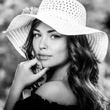 Black-white outdoor portrait of beautiful young woman in classic hat Stock Photo