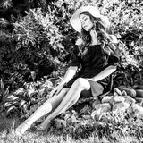 Black-white outdoor portrait of beautiful young woman in classic hat Stock Image