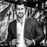 Black-white outdoor portrait of elegant handsome man in classical grey suit near wooden fence.  stock photography