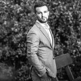 Black-white outdoor portrait of elegant handsome man in classical grey suit poses outdoor.  royalty free stock photography