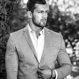 Black-white outdoor portrait of elegant handsome man in classical grey suit poses outdoor.  stock images
