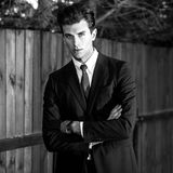 Black-white outdoor portrait of elegant handsome man in classical suit near wooden fence Royalty Free Stock Photography