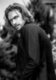Black-white outdoor portrait of elegant long hair handsome man stock photos
