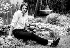 Black-white outdoor portrait of elegant long hair handsome man siting near pond Royalty Free Stock Photos