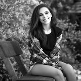 Black-white outdoor portrait of siting beautiful young brunette woman Royalty Free Stock Photos