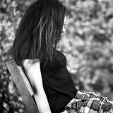 Black-white outdoor portrait of siting beautiful young brunette woman Royalty Free Stock Image