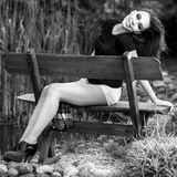 Black-white outdoor portrait of siting beautiful young brunette woman Stock Photos