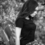 Black-white outdoor portrait of siting beautiful young brunette woman Stock Images