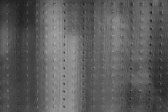Black and white outlines behind frosted glass. Matte corrugated glass, behind which black-and-white, blurred, vertical, unclear outlines. Texture, shiny surface stock image
