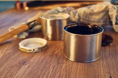 Closeup on paint cans, brush and rag, tools for painting. Black and white paint bucket with brush and dirty rag on wooden background royalty free stock photo