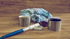 Paint cans, brush and rag, tools for painting. Black and white paint bucket with brush and dirty rag on wooden background royalty free stock photography