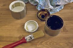Paint cans, brush and rag, tools for painting. Black and white paint bucket with brush and dirty rag on wooden background stock photography