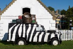 Black and White Painted Old Vintage Car Loaded Old Case Electronic Equipments Stays on Green Grasses Royalty Free Stock Image