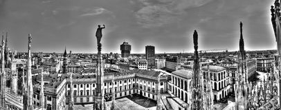 Black and white panorama photo of marble statues of Cathedral Duomo di Milano on piazza,Milan cityscape and Royal Palace of Milan Stock Photos