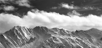 Black and white panoramic view on snow winter mountains and sunl Stock Photos