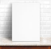 Black White paper poster lean at white ceramic tiles wall and ma. Rble table,Template mock up for adding your design royalty free stock photo
