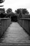 Black and White path across a wooden bridge. A rustic wooden foot bridge with parallel handrails lies ahead stock image