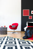 Sophisticated bedroom with red furniture. Black and white patterned carpet in sophisticated bedroom with red furniture and metal table Stock Image