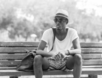 Black and White lifestyle fashion portrait. Stylish young african man sitting alone on a park bench wearing sunglasses and wicker. Black and white photo of an stock images
