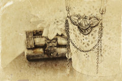 Black and white photo of antique vintage necklace on wooden table. Royalty Free Stock Photos