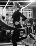 Black and white photo of the athletic girl dressed in a black sportswear running on the treadmill in the modern gym stock images