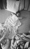 Black and white photo of baby boy sleeping on parents bed Royalty Free Stock Image