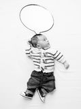 Black and white photo of baby boy with speech bubble lying on be Stock Image